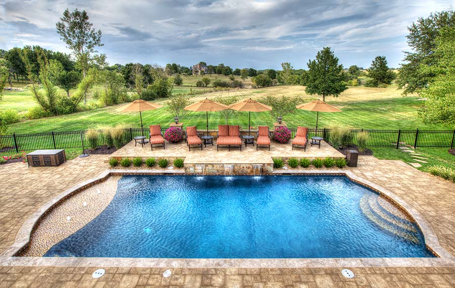 A pool with entertainment centers, outdoor kitchens, fountains, and waterfalls built by Backyard by Design Kansas City