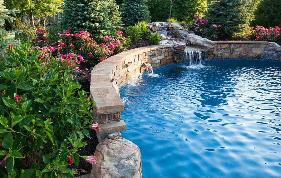 A custom build backyard and custom lighting system and pool by Backyard by Design Kansas City