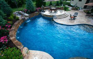 A custom build backyard and custom lighting system and pool by Backyard by Design Kansas City