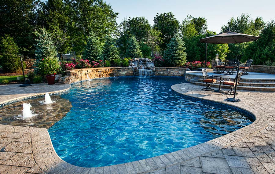 A custom pool with water features, water fall, and patio
