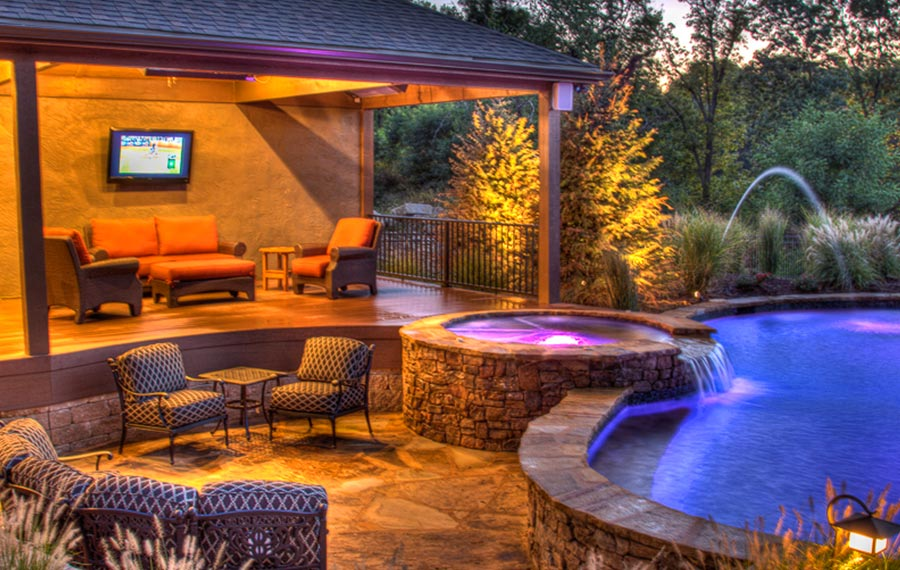 An Entertainer's Delight in Parkville pool and spa with waterfall and fountains with outdoor living space by Backyard by Design KC