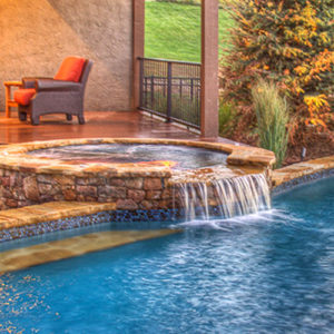 Image of spa attached to pool in front of a cabana