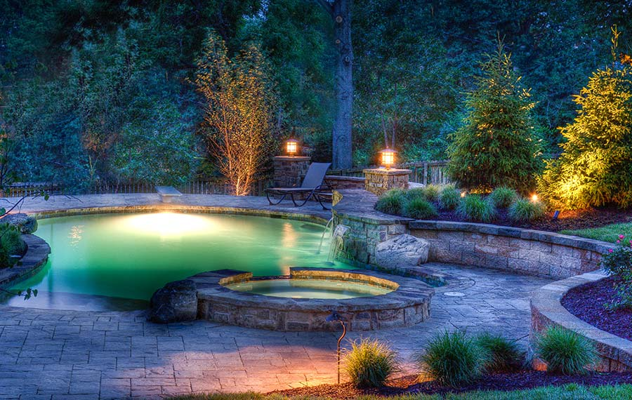 A beautifully lit backyard pool resort by Backyard by Design