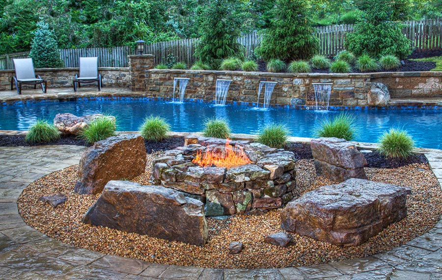 A firepit in front of a pool with waterfalls