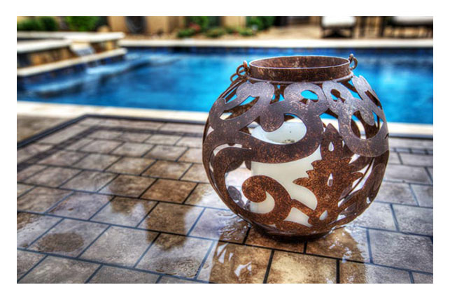 Image of iron votive on a beautiful tile table in front of a Backyard by Design Pool