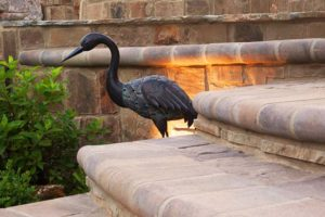 Image of iron heron by stonework steps