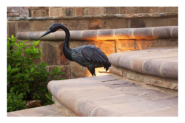 Image of iron heron by stonework steps