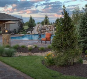 A hardscaped patio and waterfall from backyard by design