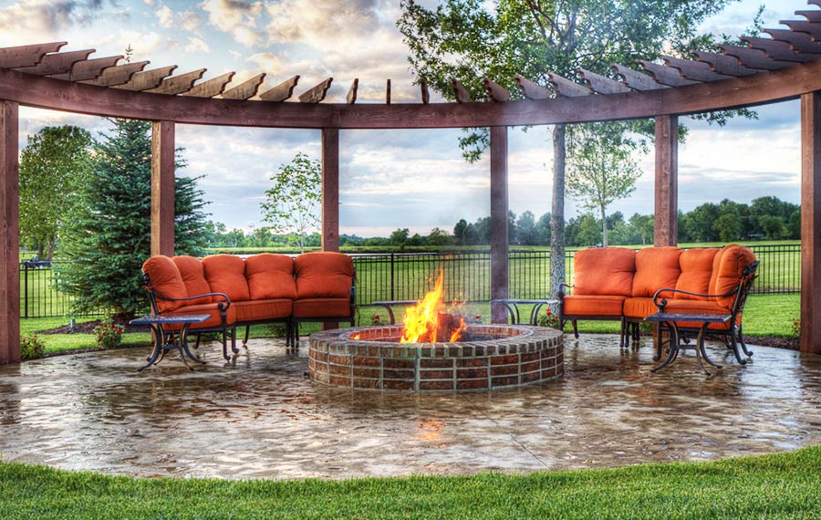 A beautiful backyard fire pit fire feature designed by Backyard by Design KC