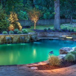 A well lit backyard pool at night with spa