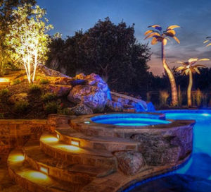 A spa leading into a pool at night, well lit artificial palm trees