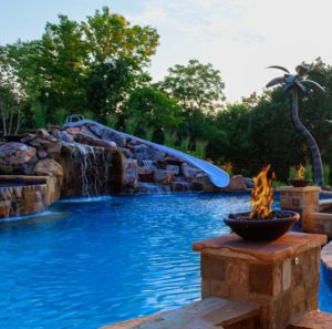 Waterfall, fire, and waterslide features by Backyard by Design Kansas City