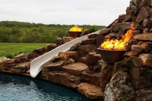 A slide leading into a pool with fire features