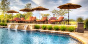 A sun deck next to a pool with water features