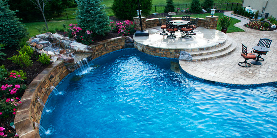 A custom backyard pool with waterfall and patio